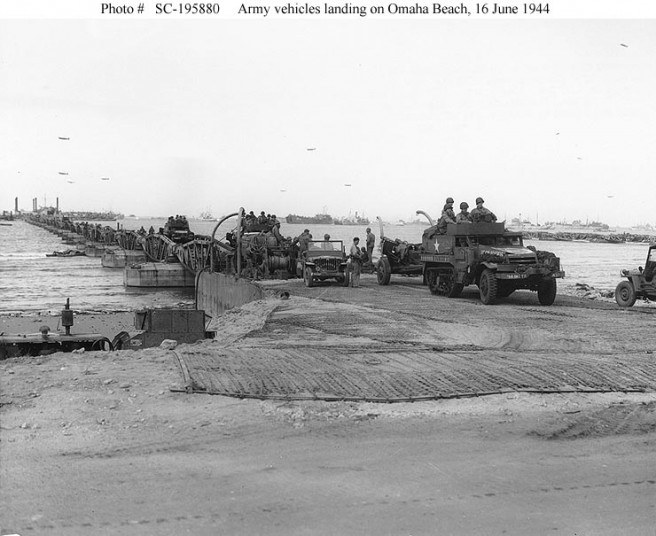 U.S. Army vehicles roll ashore on one of the floating causeways of the